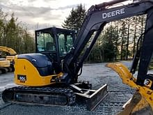 Mini excavator with a thumb in rural BC